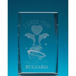 Безцветен стъклен куб с триизмерно гравирани два делфина върху глобус и сърце