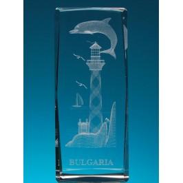 Безцветен стъклен куб с триизмерно гравирани фар с платноходка и делфин