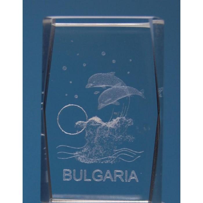 Безцветен стъклен куб с триизмерно гравирани два делфина над вълна и надпис България