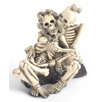 Сувенирна фигурка - два прегърнати скелета, седнали на горски дънер