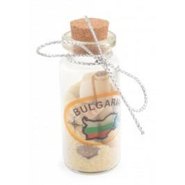 Сувенирна стъклена бутилка пълна с цветен пясък, рапани и мидички